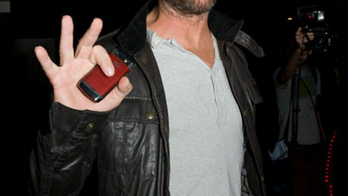 The actor was photographed carrying his red colored Blackberry at an airport.